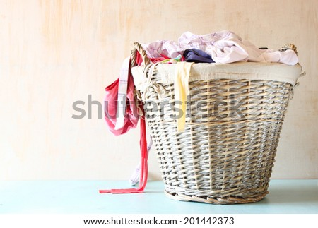 laundry basket full with clothes.   - stock photo