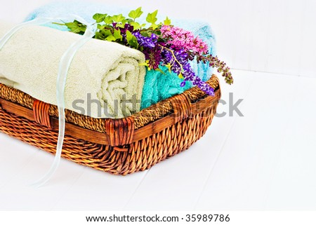 Laundry basket with fresh clean towels and a bouquet of flowers on a white beadboard. - stock photo