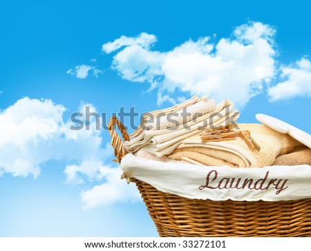 Laundry basket with towels against a blue sky - stock photo