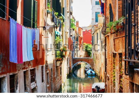 Laundry drying on clothesline above canal of Venice. View of the Rio de le Becarie Canal and the Ponte Raspi o Sansoni from the Ponte de Ledo Spade in Venice, Italy. - stock photo