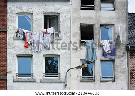 Laundry hanging from an upper story clothesline on a building in an immigrant neighborhood in Verviers, Belgium - stock photo