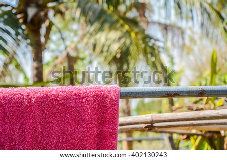 Laundry hanging on a clothesline. Dry Bath red towels on rack nature Background.Sun Dried washed  in bright clear day - stock photo