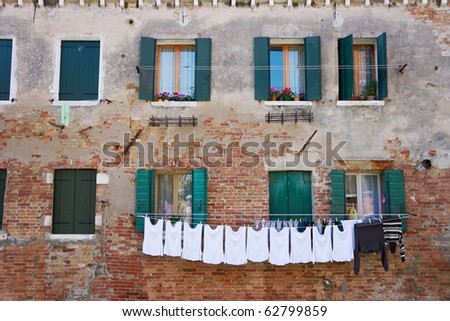Laundry hanging out of a typical Venetian facade. Italy - stock photo