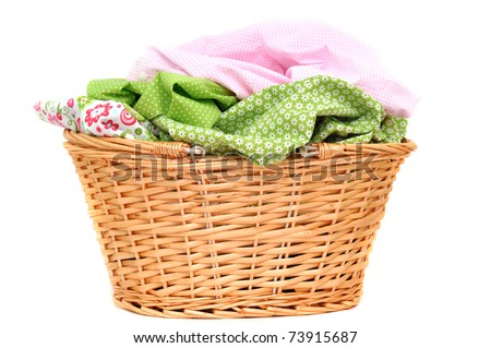 Laundry in a wicker basket, isolated on white - stock photo
