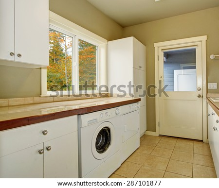 Laundry room with cabinets, tile counters, washer, and dryer. - stock photo