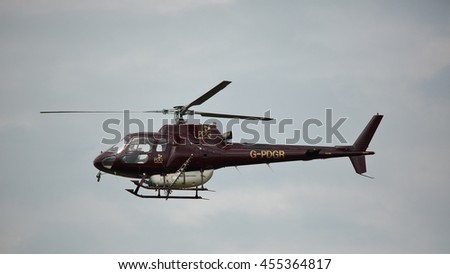 LAURIESTON, DUMFRIES AND GALLOWAY, SCOTLAND â?? JULY 20: Helicopter in flight ready to spray pesticide and fertiliser in Laurieston, Dumfries and Galloway, Scotland on 20 July 2014 - stock photo