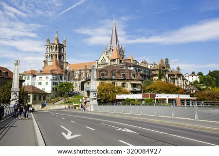 LAUSANNE, SWITZERLAND - SEPTEMBER 12, 2015 Lausanne Cathedral (Notre Dame) seen in the distance, built in Gothic style and it was completed in 1235, was consecrated in 1275 - stock photo
