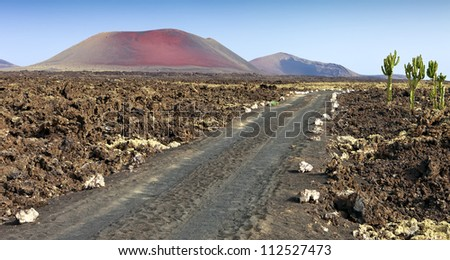Lava Fields and a road leading to the mountains of fire, Timanfaya National Park in Lanzarote Island, Spain - stock photo