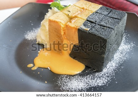 Lava toast with salted egg cream and bread on black plate  and whipping cream. - stock photo