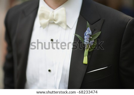 Lavender boutonniere flower on suit jacket of wedding groom - stock photo