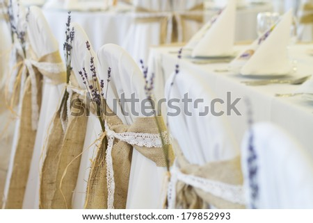 lavender flower decoration on wedding chairs cover - stock photo