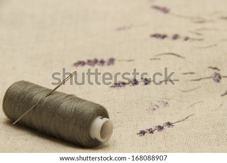 lavender flowers embroidered on linen fabric with needle and thread - stock photo