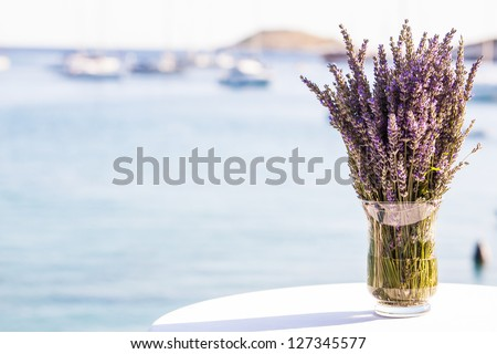 Lavender flowers in a glass vase on a table by the ocean. - stock photo