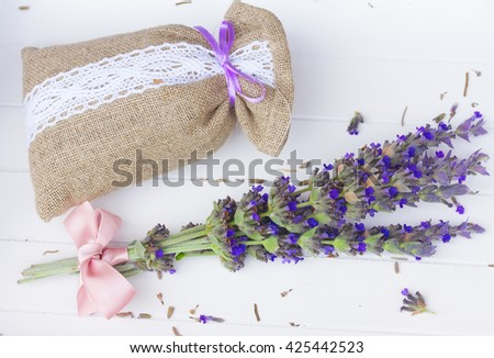 Lavender  fresh and dry flowers in pouch on white wooden table - stock photo
