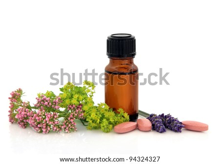 Lavender herb, valerian, ladies mantle flower heads and aromatherapy bottle with alternative medicine pills over white background. - stock photo