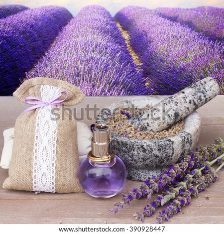 Lavender herbal water in a glass bottle with fresh and dry flowers on  gray table - stock photo