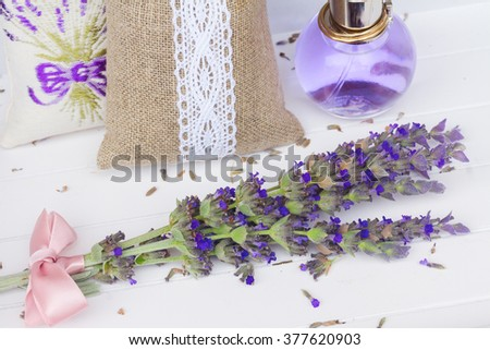 Lavender herbal water with fresh and dry flowers on white wooden table - stock photo