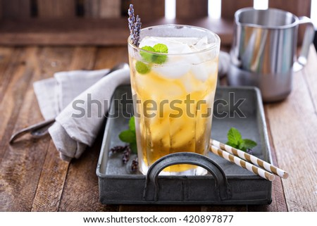 Lavender iced tea in tall glass with ice - stock photo