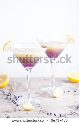 Lavender martini with vodka and fresh lemon juice on the light background - stock photo