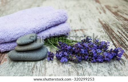 Lavender, massage stones  and towels on a wooden background - stock photo