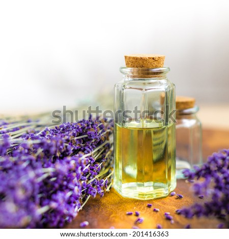 Lavender oil for spa on a wooden desk with lavender flowers - stock photo