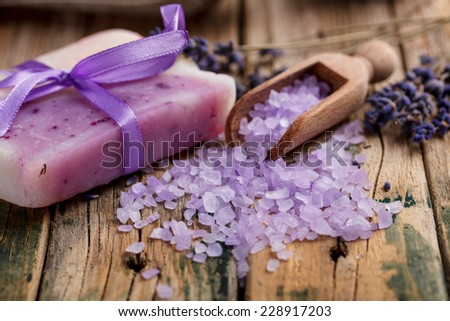 Lavender soap and salt on rustic wooden board - stock photo