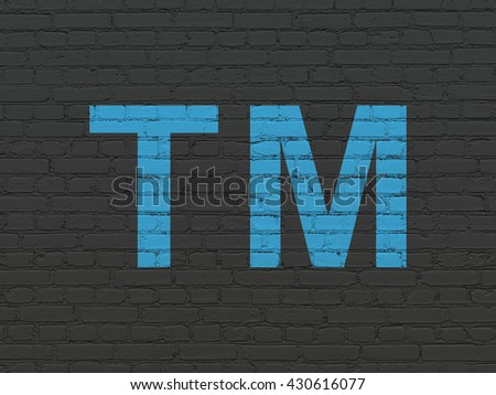 Law concept: Painted blue Trademark icon on Black Brick wall background - stock photo
