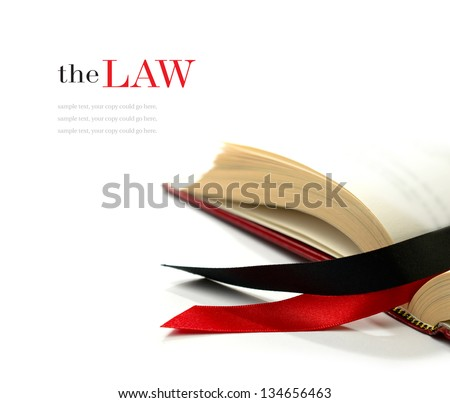 Law concept stock image. Silk ribbons on a opened legal book against a white background. Copy space. - stock photo