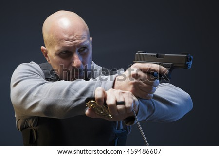 Law enforcement undercover agent with gun and a badge. - stock photo