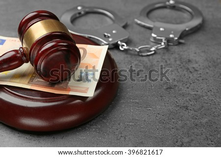 Law gavel with euro and handcuffs on grey background, closeup - stock photo