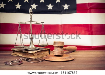 Law scales, judge gavel, handcuff, old book front USA flag. Symbol of justice. Retro style photo - stock photo