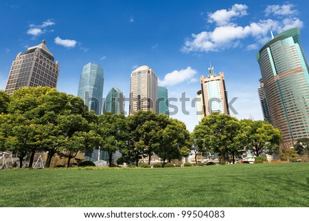 lawn and trees with modern building background in shanghai greenbelt park - stock photo