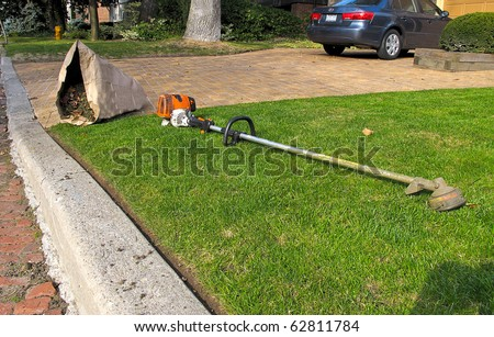 Lawn care equipment and garden sac in residential neighborhood - stock photo
