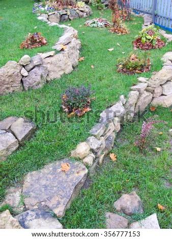 Lawn limestone terraces with cultivar decorative shrubs in the autumn garden - stock photo
