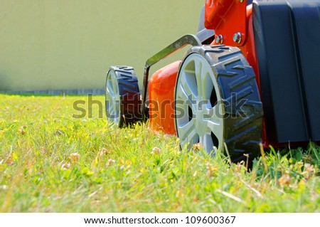 lawn mower and green grass / lawn mower / gardening - stock photo