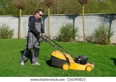 lawn mower man working on the backyard - stock photo