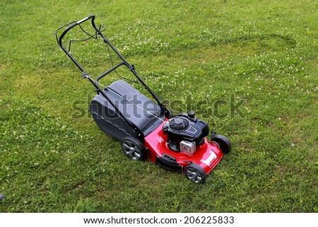 Lawn mower on the grass during the summer day - stock photo