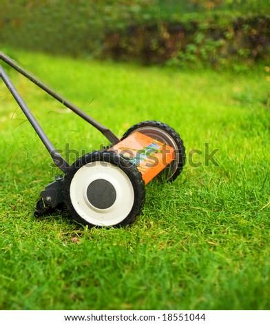 Lawnmower cutting grass - stock photo