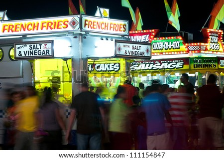 LAWRENCEVILE, GA, USA - SEPTEMBER 24:  Unidentified patrons walk amongst a variety of fast food vendors at the Gwinnett County Fair in Lawrenceville on September 24, 2011 - stock photo