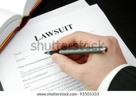 lawsuit form with attorney's hand and pen - stock photo