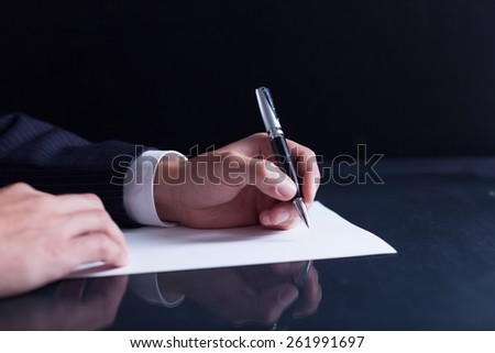 Lawyer. Businessman writing a letter, notes or correspondence or signing a document or agreement, close up view of his hand and the paper - stock photo
