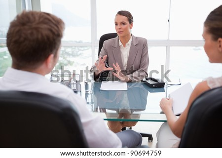 Lawyer explaining legal situation to her clients - stock photo