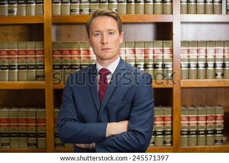 Lawyer frowning in the law library at the university - stock photo