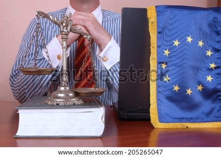 Lawyer in the office with decorative scales of Justice on the book and EU flag - stock photo
