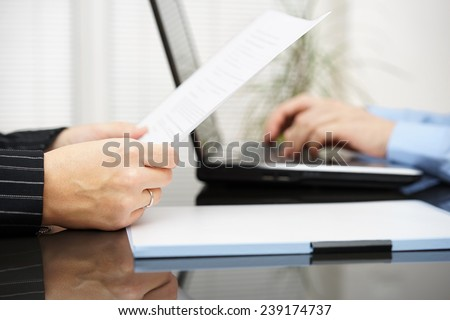 Lawyer is reading contract and business client is typing on laptop - stock photo