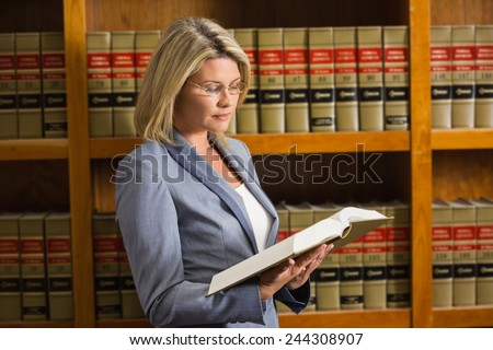 Lawyer reading book in the law library at the university - stock photo