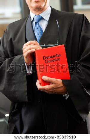 Lawyer with civil law code - only torso to be seen, close-up - stock photo
