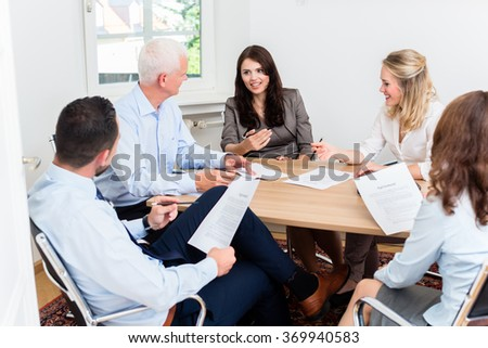 Lawyers having team meeting in law firm reading documents - stock photo
