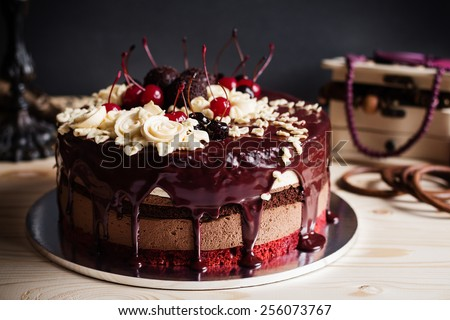 Layer cake decorated with chocolate glaze, cream flowers and cherries on dark background with retro decorations - stock photo