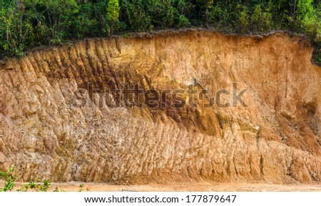 Layer of soil Front loader strips all side of a hill. - stock photo